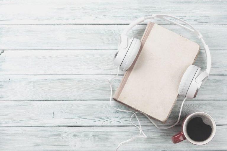 Photo of a cream colored book, white headphones and a mug of coffee.